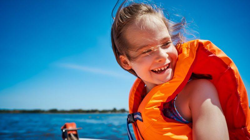 Barn i flytväst som åker båt