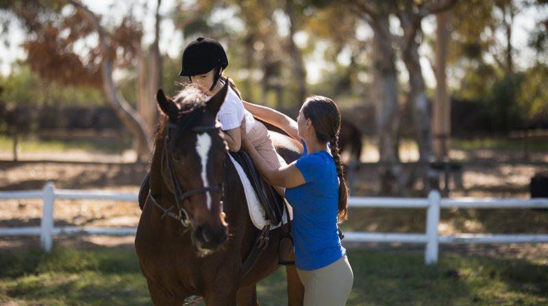 Instruktör som hjälper ett barn som sitter på häst
