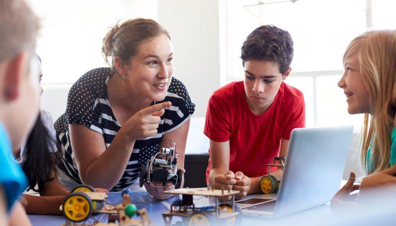 Barn som som bygger leksaksbilar med en vuxen person som instruktör